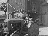 Auf dem Bild sieht man das Jahr 1959. Im Vordergrund sieht man eine Traktor der Marke Eicher. Auf dem Traktor sitzen Opa Heinrich und der dreijährige Heinfried Peth.
